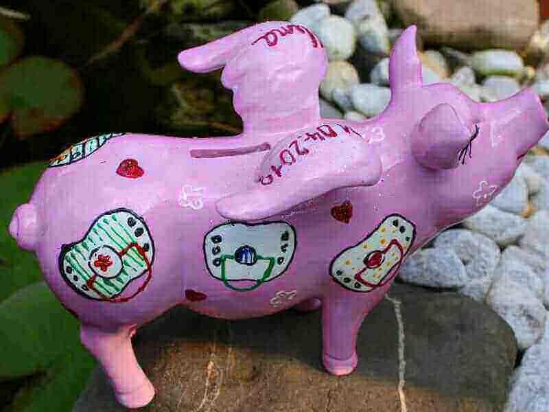 Zur Geburt ein Sparschwein mit Schnullern